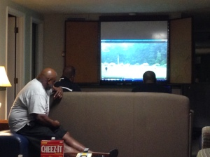 Coaches watching practice film in the cabin late at night